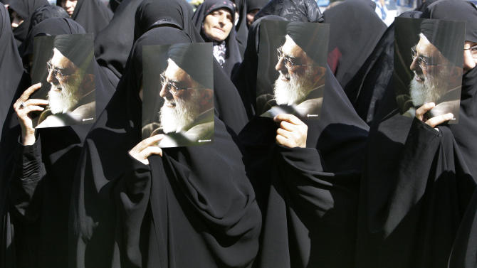 """FILE -- In this Saturday, Sept. 29, 2012 file photo, Iranian seminary students hold posters of supreme leader Ayatollah Ali Khamenei at a demonstration of clerics to protest the film ridiculing Islam's Prophet Muhammad, in Tehran, Iran, Saturday, Sept. 29, 2012. A religious decree issued by Iran's supreme leader banning nuclear weapons is binding for the Iranian government, the Foreign Ministry said Tuesday, Jan. 15, 2013, suggesting that the edict should end the debate over whether Tehran is pursuing atomic arms. Ministry spokesman Ramin Mehmanparast said the West must understand the significance of Ayatollah Ali Khamenei's edict for Iran, saying """"there is nothing higher than the exalted supreme leader's fatwa to define the framework for our activities in the nuclear field."""" (AP Photo/Vahid Salemi, File)"""