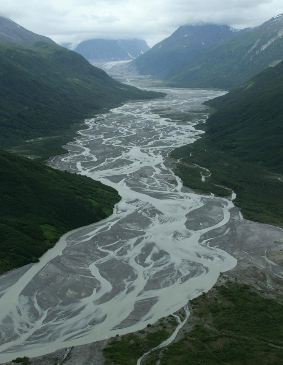 This photo taken July 5, 2013, in Lake Clark Pass near Port Alsworth, Alaska, shows a river valley cutting through the mountains. Many float planes will fly through the pass as they take day-trippers to Katmai National Park and Preserve to see the brown bears. (AP Photo/Mark Thiessen)