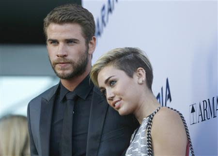 "Hemsworth poses with Cyrus at premiere of ""Paranoia"" in Los Angeles"