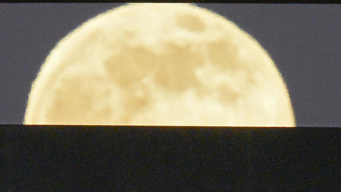Fans sit as the moon rises behind them during the Los Angeles Angels' baseball game against the Pittsburgh Pirates, Saturday, June 22, 2013, in Anaheim, Calif. (AP Photo/Mark J. Terrill)