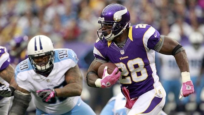 Minnesota Vikings running back Adrian Peterson, right, runs from Tennessee Titans defensive tackle Jurrell Casey, left, during the first half of an NFL football game on Sunday, Oct. 7, 2012, in Minneapolis. (AP Photo/Genevieve Ross)