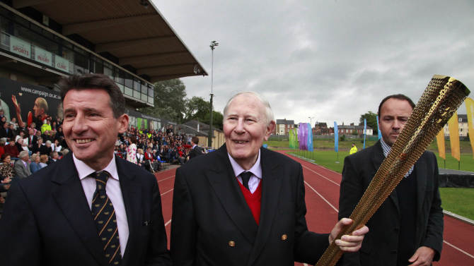 Sebastian Coe, left, chairman of the London 2012 Organizing Committee, stands with Sir Roger Bannister, after he passed the Olympic Flame to a torchbearer on the running track at Iffley Road Stadium in Oxford, England, Tuesday July 10, 2012. Bannister was the first person ever to run a sub four-minute-mile, on May 6, 1954, at this track in Oxford. Bannister returned to the site of his greatest sporting achievement, to participate in the Olympic Torch relay as the Olympic flame is carried around the country to the opening ceremony of the 2012 London Olympic Games. (AP Photo/Lefteris Pitarakis)