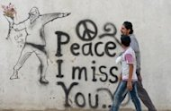 Syrian youths walk past graffiti in the rebel-held Syrian city of Minbej. Rebels drove the much-feared Syrian security forces out of the northern city of Minbej in July, and are now slowly rebuilding its police force to combat a rise in crime