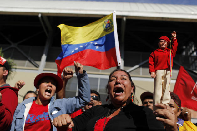 Supporters of Venezuela's late President Hugo Chavez shout slogans as they line up outside the military academy where a funeral ceremony will take place for him in Caracas, Venezuela, Friday, March 8,