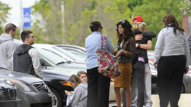 Hofstra University students gather near the house where another student and an armed intruder were killed during an overnight house break-in next to the campus, early Friday, May 17, 2013, in Uniondale, N.Y. (AP Photo/ Louis Lanzano)
