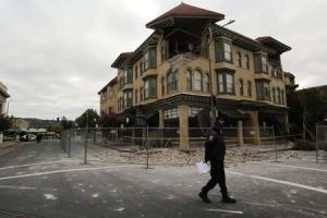 A security officer patrols an area in front of a building damaged by Sunday's magnitude 6.0 earthquake in Napa