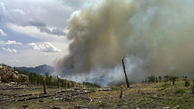 This Tuesday June 5, 2012 photo provided by the Wyoming State Forestry Division shows smoke rising from a wildfire burning in a rugged area of the Medicine Bow in southeast Wyoming. The fire, which is believed to have been started by lightning on Sunday night, has burned about 3,500 acres about 20 miles northwest of Wheatland. About 120 firefighters, aided by helicopters and air tankers, are on the scene with more crews expected Wednesday. (AP Photo/Wyoming State Forestry Division)