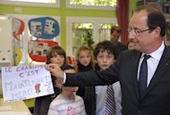 "French President Francois Hollande (right) holds a drawing reading: ""The change is now! Thank you"" at a school in Dieudonne, north of Paris, this week. France votes in the opening round of a parliamentary election on Sunday with ollande's Socialists and their left-wing allies expected to emerge with a clear majority"