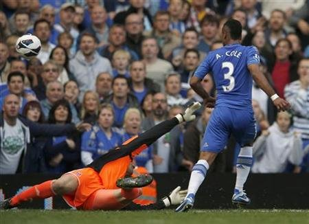 Chelsea's Cole chips ball over Stoke City goalkeeper Begovic to score his goal during their English Premier league soccer match at Stamford Bridge in London