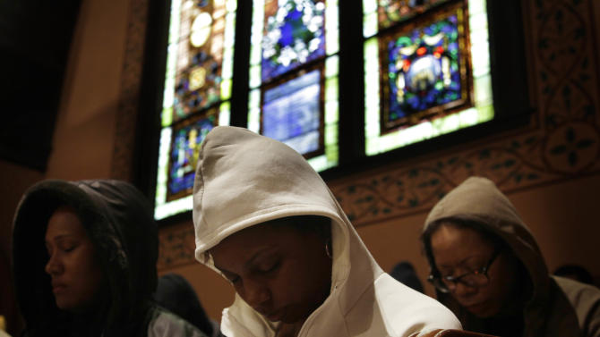 Congregants bow their heads in prayer during a service at Middle Collegiate Church in New York, Sunday, March 25, 2012. Church-goers were invited to wear hoodies to services to show their support for justice in the case of Trayvon Martin, an unarmed black teenager who was wearing a hoodie on the night he was killed by a neighborhood watch captain in Florida. (AP Photo/Seth Wenig)