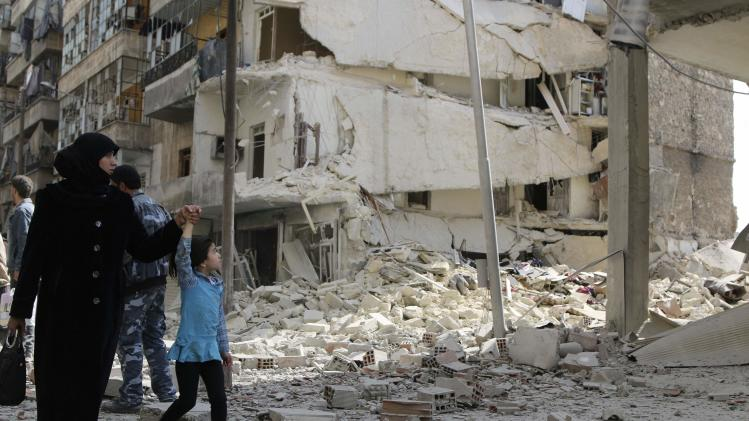 Residents inspect damage after what activists said was airstrike by forces loyal to President al-Assad in Aleppo