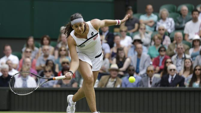 Marion Bartoli of France plays a return to Kirsten Flipkens of Belgium in a Women's singles semifinal match at the All England Lawn Tennis Championships in Wimbledon, London, Thursday, July 4, 2013. (AP Photo/Anja Niedringhaus)