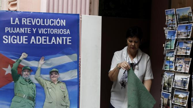 A woman who sells postcards at a government store shakes out a rug at a shop where the entry is decorated with a poster of Fidel Castro, left, and his brother, Cuba's President Raul Castro, in Havana, Cuba, Tuesday, Nov. 13, 2012. The U.N. General Assembly on Tuesday voted overwhelmingly to condemn the U.S. commercial, economic and financial embargo against Cuba for the 21st year in a row. The embargo was first enacted in 1960 following Cuba's nationalization of properties belonging to U.S. citizens and corporations. (AP Photo/Franklin Reyes)