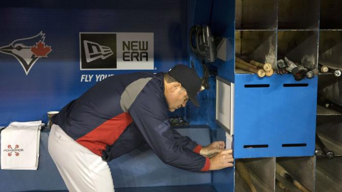 Boston Red Sox manager John Farrell tapes up team information in the away team dug out as he prepares to face the Toronto Blue Jays in a baseball game in Toronto on Saturday, April 6, 2013.(AP Photo/The Canadian Press, Chris Young)