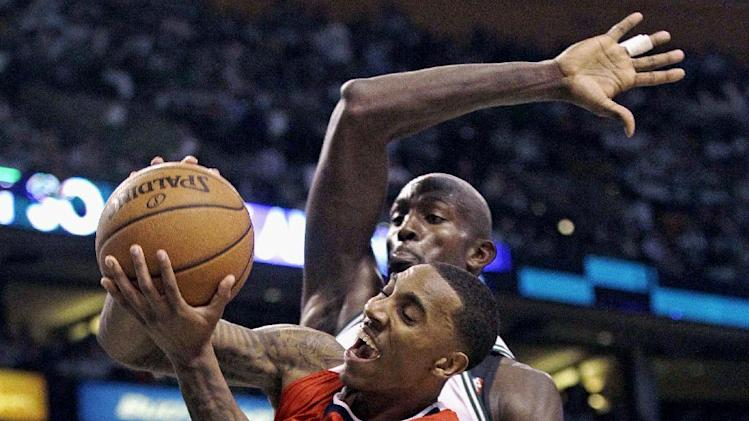 Atlanta Hawks guard Jeff Teague, front, gets past Boston Celtics forward Kevin Garnett, who starts to swipe his arm on a block, during the second half of Game 3 of an NBA first-round playoff basketball series, Friday, May 4, 2012, in Boston. (AP Photo/Charles Krupa)