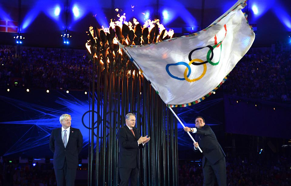 London Mayor, Boris Johnson, left, watches the Mayor of Rio de Janeiro, Eduardo Paes, right, wave the Olympic flag as the International Olympic Committee President Jacques Rogge applauds during the Closing Ceremony of the 2012 Summer Olympics on Sunday, Aug. 12, 2012, in London. (AP Photo/Jeff J Mitchell, Pool)