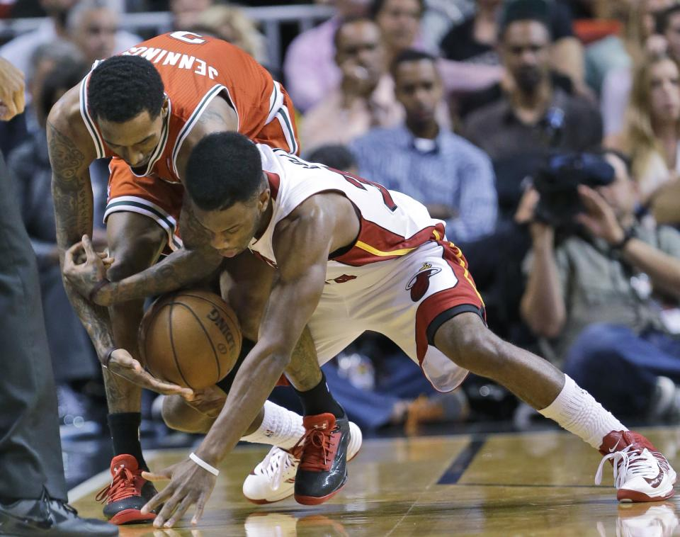 Milwaukee Bucks guard Brandon Jennings, left, and Miami Heat guard Norris Cole scramble for a loose ball during the first half of an NBA basketball game, Tuesday, April 9, 2013, in Miami. (AP Photo/Wilfredo Lee)