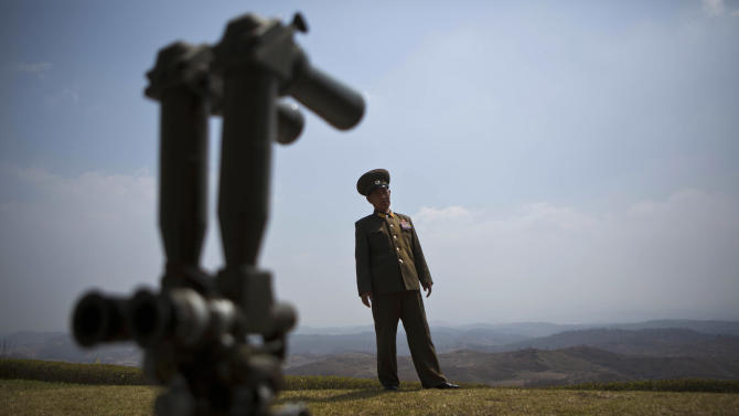 North Korean army Col. Kim Chang Jun stands behind field binoculars on a hilltop overlooking the demilitarized zone which separates the two Koreas, south of Kaesong, North Korea Wednesday, April 24, 2013. (AP Photo/David Guttenfelder)