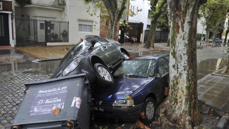 Cars and garbage containers lay piled up after flash flooding caused damage overnight in Buenos Aires, Argentina, Tuesday, April 2, 2013. According to city officials, at least five people were killed during the heavy rains. (AP Photo/Leonardo Zavattaro, Telam)