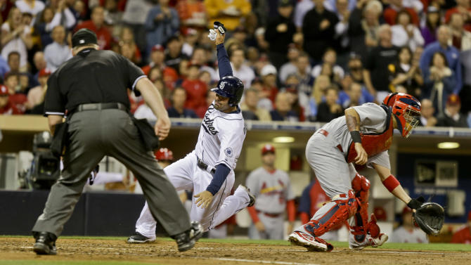 San Diego Padres' Carlos Quentin goes into a slide as he reaches for home plate while St. Louis Cardinals catcher Yadier Molina waits on the late throw in the sixth inning of a baseball game in San Diego, Monday, May 20, 2013. The umpire is Bill Miller.  (AP Photo/Lenny Ignelzi)