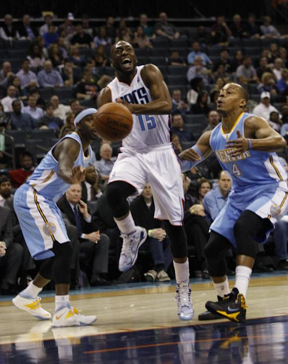 Charlotte Bobcats guard Kemba Walker (15) loses control of the ball as he drives pas Denver Nuggets guard Randy Foye, right, during the first half of an NBA basketball game in Charlotte, N.C., Monday,