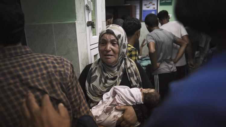 A Palestinian woman holds an infant, whom medics said was injured in an Israeli shelling at a U.N-run school sheltering Palestinian refugees, at a hospital in the northern Gaza Strip