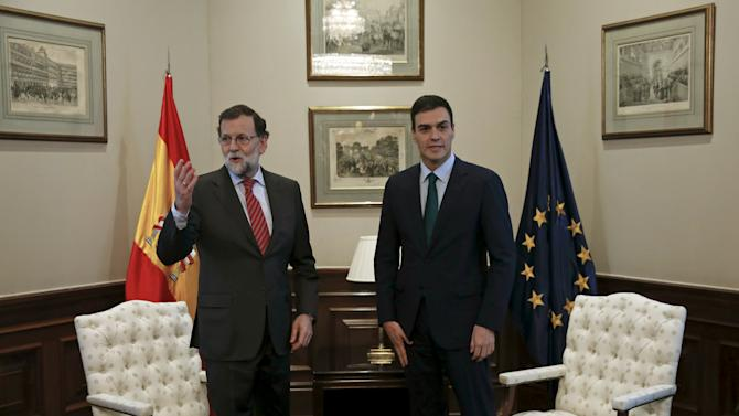 Spain's acting PM Rajoy gestures beside PSOE leader Sanchez at the start of their meeting at Parliament in Madrid