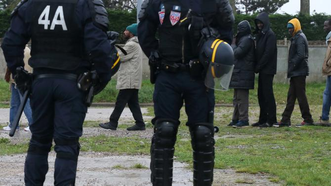 French riot policemen stand guard during daily food distribution for migrants in Calais