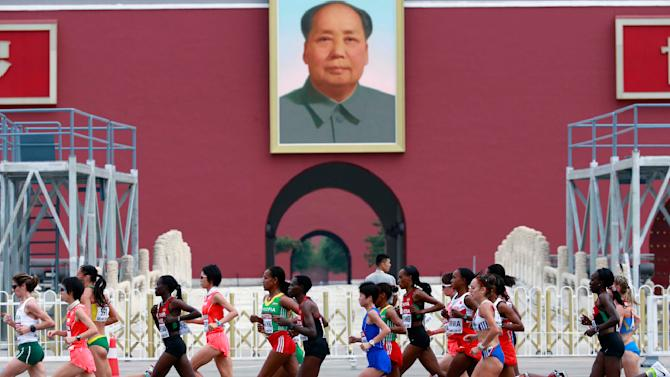 Athletes run past a portrait of late Chinese Chairman Mao during the women's marathon at the 15th IAAF Championships in Beijing