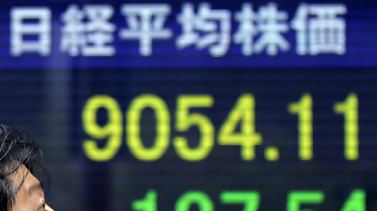 A man walks by the electronic stock board of a securities firm showing Japan's Nikkei 225 index, top left, dropped 127.54 points to 9,054.11 in Tokyo Wednesday, May 9, 2012. Asian stock markets fell Wednesday, spooked by disappointing U.S. corporate earnings and fears that political turmoil in debt-crippled Greece is pushing it closer to financial disaster. (AP Photo/Itsuo Inouye)