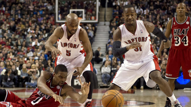 Miami Heat forward Chris Bosh, left battles for a loose ball with Toronto Raptors guards John Lucas III (5) and Terrence Ross (31) during first half NBA baketball action in Toronto Sunday Feb. 3, 2013. (AP Photo/THE CANADIAN PRESS, FRANK GUNN)