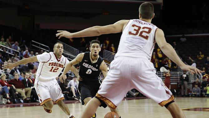 Colorado's Askia Booker, center, drives between Southern California's Julian Jacobs, left, and Nikola Jovanovic during the first half of an NCAA college basketball game, Thursday, Jan. 29, 2015, in Los Angeles. Booker scored a career-high 43 points as Colorado won in triple overtime, 98-94. (AP Photo/Jae C. Hong)