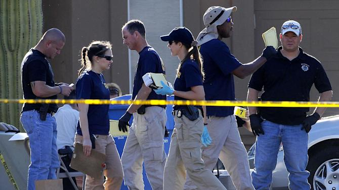 Police officers and FBI agents walk inside the police tape outside a crime scene Thursday, May 3, 2012 in Gilbert, Ariz. Gilbert police spokesman Sgt. Bill Balafas said Thursday that police believe Jason Todd Ready, 39, a former Marine with ties to neo-Nazi and Minutemen groups, shot four people Wednesday and then took his own life in a suburban Phoenix home. (AP Photo/Matt York)