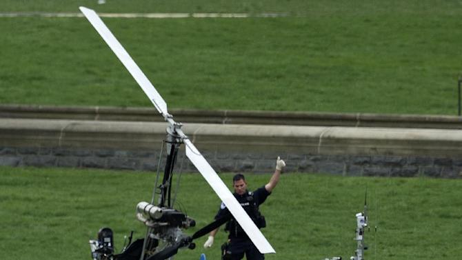 A Capitol Police officer flashes a thumbs up after inspecting the small helicopter a man landed on the West Lawn of the Capitol in Washington, Wednesday, April 15, 2015. Police arrested a man who steered his tiny, one-person helicopter onto the West Lawn of the U.S. Capitol Wednesday, astonishing spring tourists and prompting a temporary lockdown of the Capitol Visitor Center. Capitol Police didn't immediately identify the pilot or comment on his motive, but a Florida postal carrier named Doug Hughes took responsibility for the stunt on a website where he said he was delivering letters to all 535 members of Congress in order to draw attention to campaign finance corruption.   (AP Photo/Manuel Balce Ceneta)