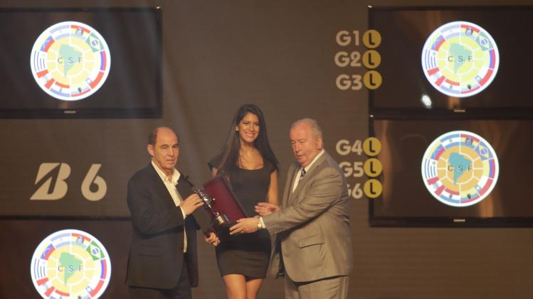 Argentina's former soccer player Hector Ricardo Bochini receives an award from President of the Argentine Football Association (AFA) Julio Grondona during the draw for the 2014 Copa Libertadores at the CONMEBOL headquarters on the outskirts of Asuncion