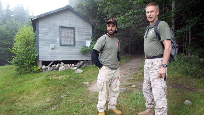 In this photo taken Wednesday Aug. 6, 2014, Afghan native Fahim Fazli, left, and retired Marine Michael Moffett are seen at the base of Mount Washington, N.H. before ascending the mountain via the Ammonoosuc Ravine Trail. The two are co-authors of a book about Fazli's life as an Afghan native who fled his country, became a U.S. Citizen, a Hollywood actor who played roles as a Middle eastern terrorist, and returned to Afghanistan to be a translator for U.S. Marines. The two hiked Mount Washington in hopes the Presidential Range would be a stand in for a movie for Asia's Hindu Kush mountains. (AP Photo/Jim Cole)