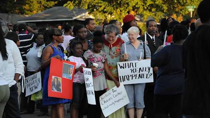 Supporters of Chavis Carter and his family, including Taelor Chavis, second from left, 9, and Kimi Miller, center, 9, hold signs during the candlelight vigil held in honor of Carter on Monday, Aug. 6, 2012, at the First Baptist Church on Kitchen Street in Jonesboro, Ark. (AP Photo/The Jonesboro Sun, Krystin McClellan)