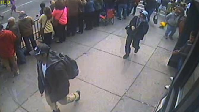 This image taken from video released by the FBI on Thursday, April 18, 2013 shows what the FBI are calling suspect number 1, front, in black cap, and suspect number 2, in white cap, back right, walking near each other through the crowd in Boston on Monday, April 15, 2013, before the explosions at the Boston Marathon. (AP Photo/FBI)