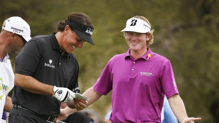 Brandt Snedeker, right, laughs with Phil Mickelson as they talk about Mickelson's long birdie putt at the seventh hole during the final round of the Waste Management Phoenix Open golf tournament on Sunday, Feb. 3, 2013, in Scottsdale, Ariz. (AP Photo/Ross D. Franklin)