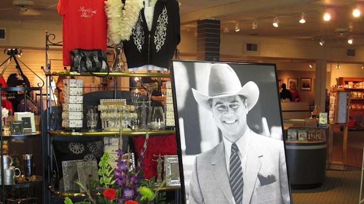"""A large portrait of Larry Hagman can be seen by a bouquet of flowers at the entrance of the gift shop at Southfork Ranch on Saturday, Nov. 24, 2012, in Parker, Texas. Officials at the ranch, the setting for the TV series """"Dallas"""" where Hagman played the infamous J.R. Ewing, placed the photo there in memory of Hagman, who died Friday, Nov. 23, 2012 in Dallas. He was 81. (AP Photo/Angela K. Brown)"""
