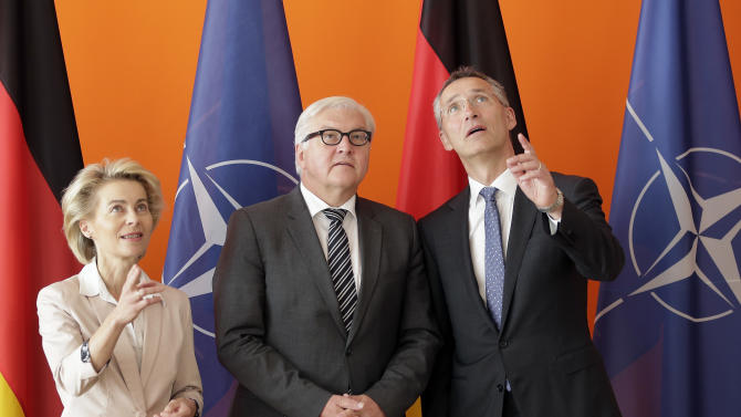 German Defense Minister Ursula von der Leyen, German Foreign Minister Frank-Walter Steinmeier and Jens Stoltenberg, Secretary General of the North Atlantic Treaty Organization,NATO, from left, look up during a photo call in Berlin, Germany, Tuesday, June 30, 2015 to mark the 60th anniversary of Germany's accessing to the NATO. (AP Photo/Michael Sohn)