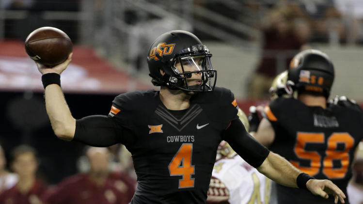 Oklahoma State quarterback J.W. Walsh (4) passes during the first half of an NCAA college football game against Florida State, Saturday, Aug. 30, 2014, in Arlington, Texas. (AP Photo/Tony Gutierrez)