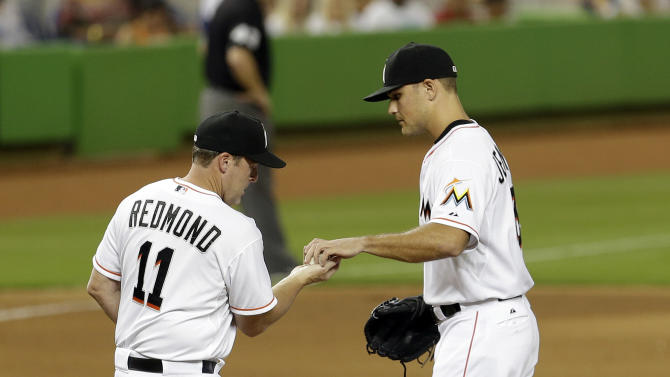Miami Marlins relief pitcher Dan Jennings, right, hands the ball to manager Mike Redmond (11) in the eighth inning of a baseball game against the Washington Nationals in Miami, Thursday, Sept. 18, 2014. The Nationals won 6-2. (AP Photo/Alan Diaz)
