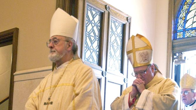 FILE - In this Aug. 28, 2002, file photo Timothy Dolan, right, bows his head behind retired Archbishop Rembert Weakland, left, as he enters The Cathedral of St. John the Evangelist in Milwaukee to be installed as the 10th Archbishop of the Milwaukee Archdiocese. The Archdiocese of Milwaukee is expected to release thousands of pages of documents related to clergy sex abuse on Monday, July 1, 2013, which church officials say include the depositions of Dolan and Weakland. (AP Photo/Dale Guldan, Pool)