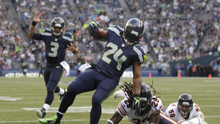 Seattle Seahawks' Marshawn Lynch (24) scores as quarterback Russell Wilson (3) reacts behind and Chicago Bears' Danny McCray hits the turf in the first half of an preseason NFL football game, Friday, Aug. 22, 2014, in Seattle