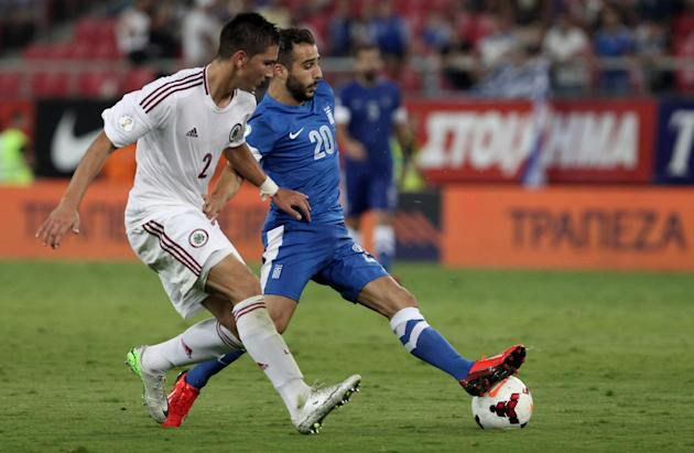 Greece's Giannis Fetfatzidis, right, and Latvia's Vitalijs Maksimenko challenge for the ball during their World Cup Group G qualifying soccer match at the Karaiskaki stadium in Piraeus port, near Athe