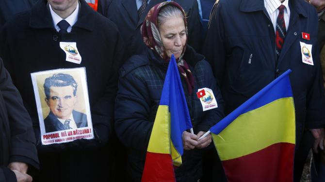 People attend a commemoration ceremony at the grave of Romania's late Communist dictator Ceausescu ceremony in a Bucharest cemetery