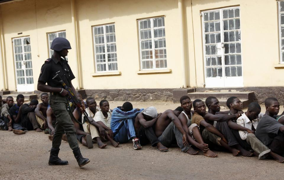 A Nigeria Police stand guard as suspected rioters await a court hearing in Kaduna, Nigeria, Wednesday, April 20, 2011. About 200 people were arraigned Wednesday in local court for taking part in the rioting that followed Nigeria's recent presidential election. (AP Photo/Sunday Alamba)