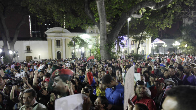Supporters of Venezuela's late President Hugo Chavez gather in Bolivar square to mourn Chavez's death in Caracas, Venezuela, Tuesday, March 5, 2013. Venezuela's Vice President Nicolas Maduro announced that Chavez died on Tuesday at age 58 after a nearly two-year bout with cancer. During more than 14 years in office, Chavez routinely challenged the status quo at home and internationally. He polarized Venezuelans with his confrontational and domineering style, yet was also a masterful communicator and strategist who tapped into Venezuelan nationalism to win broad support, particularly among the poor. (AP Photo/Ariana Cubillos)