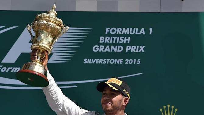 Mercedes' British driver Lewis Hamilton raises the trophy on the podium after winning the British Formula One Grand Prix at the Silverstone circuit in Silverstone on July 5, 2015